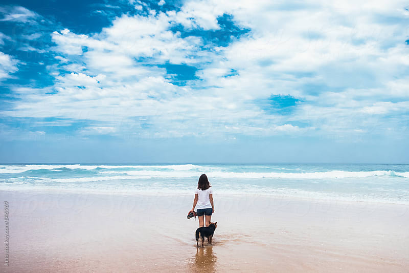 woman and her dog on a pristine isolated beach looking out to sea by Micky Wiswedel for Stocksy United