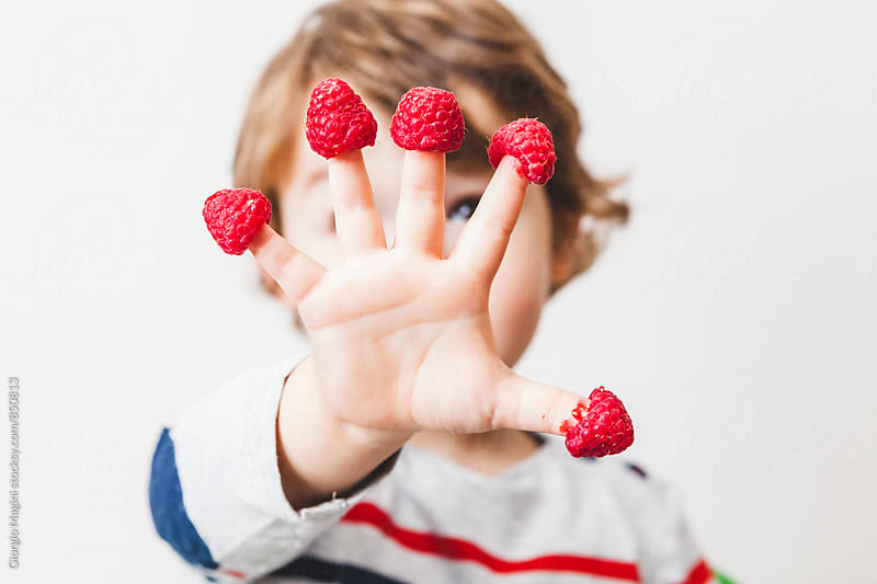 Cute Child with Raspberries on the Fingers by Giorgio Magini for Stocksy United