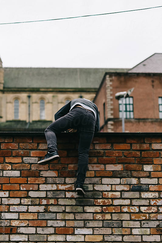 Young Man Standing on a High Wall in the City by HEX. for Stocksy United