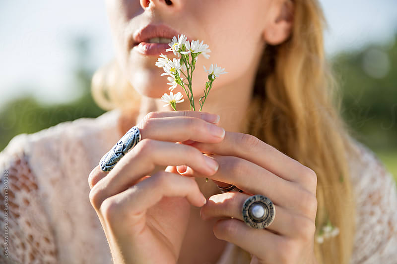 Young blonde holding a small white flower in her hands by Jovo Jovanovic for Stocksy United