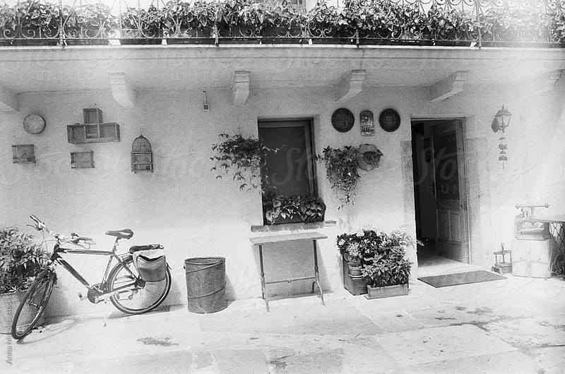 A black and white film photo of small Italian village house with a bicycle by Anna Malgina for Stocksy United