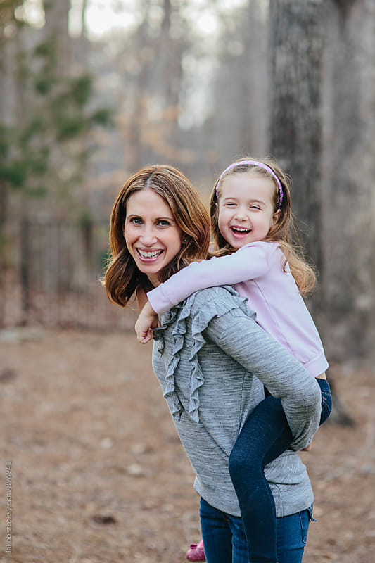 Cute young daughter on a piggy back ride with her mother by Jakob for Stocksy United