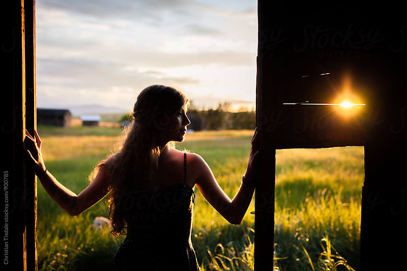 Beautiful young girl standing in doorway of a barn looking right by Christian Tisdale for Stocksy United