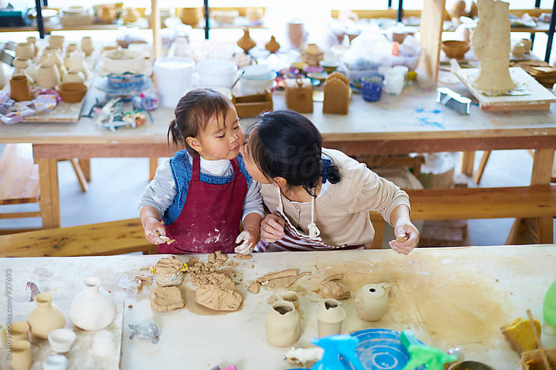 asian woman working in the pottery with her daughter by Bo Bo for Stocksy United
