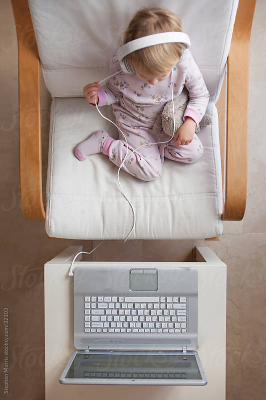 Little Girl with Headphones Watching Laptop by Stephen Morris for Stocksy United