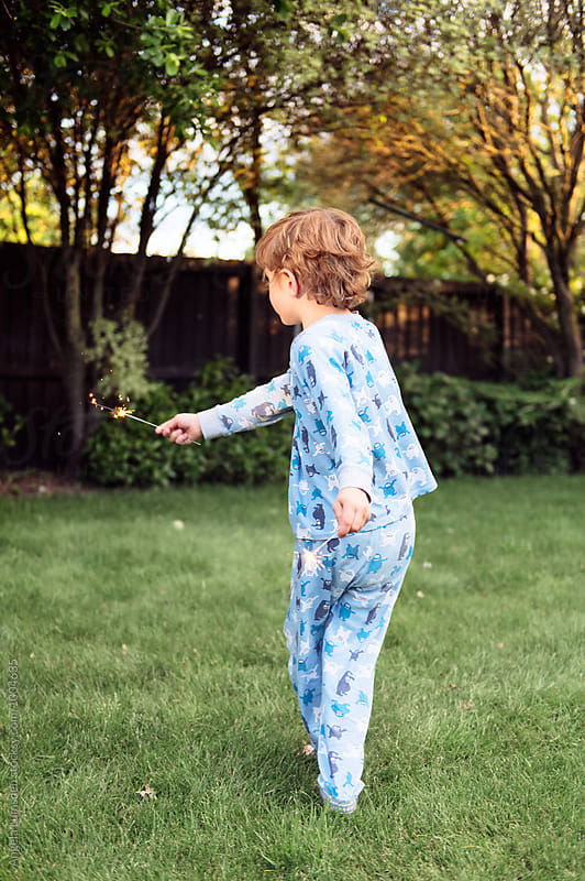 Child in pajamas twirling in the garden with a sparkler in each hand by Angela Lumsden for Stocksy United