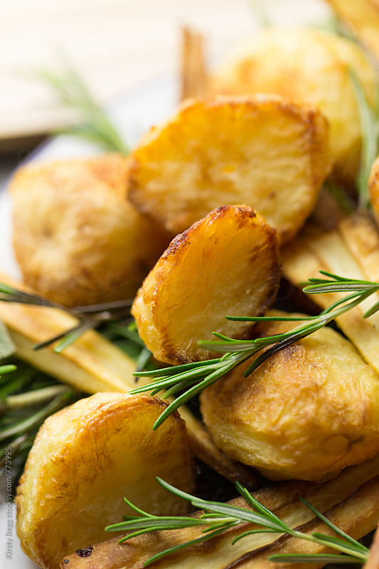 Crispy roast potatoes with fresh rosemary sprigs by Kirsty Begg for Stocksy United
