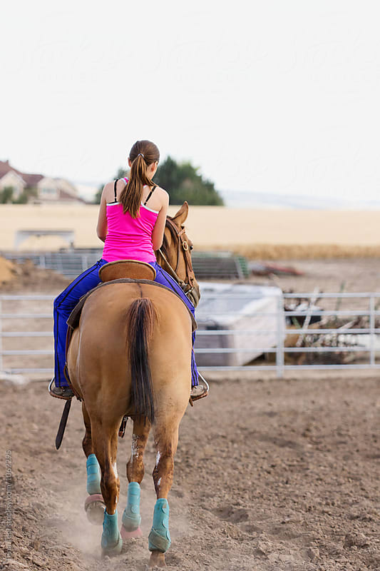 girl rides horse in arena by Tana Teel for Stocksy United