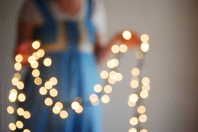 A woman holding out of focus twinkle lights by Chelsea Victoria for Stocksy United