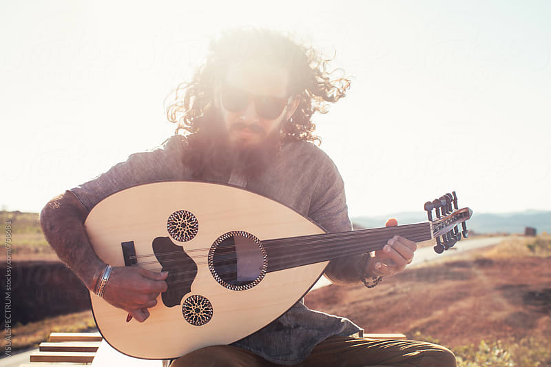 Portrait of Bearded Young Hippie Wearing Sunglasses and Playing Oud (Mandolin) by Julien L. Balmer for Stocksy United