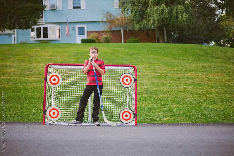 Portrait of Boy Playing Street Hockey by Raymond Forbes LLC for Stocksy United