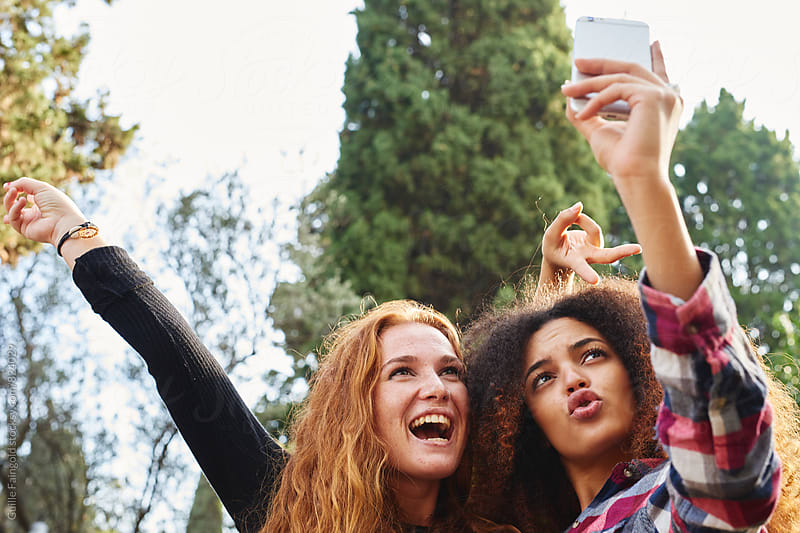 Two funny young women making faces and putting hands up while taking selfie by Guille Faingold for Stocksy United