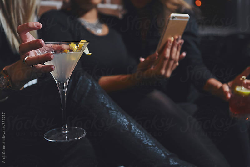 Ladies looking at a phone while drinking by Alicja Colon for Stocksy United