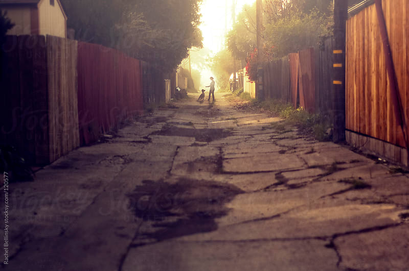 The silhouette of a woman training her dog at the end of a cracked sunlit alley by Rachel Bellinsky for Stocksy United