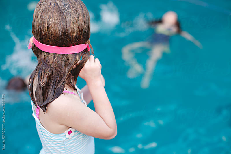 A young girl stands on the edge of a pool and  looks at her sister and brother swimming by Natalie JEFFCOTT for Stocksy United