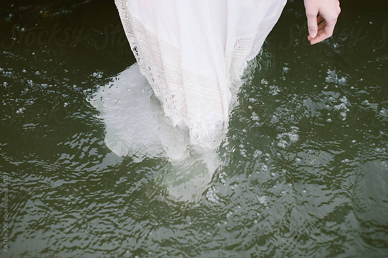 woman in a white dress standing in a murky lake by KATIE + JOE for Stocksy United