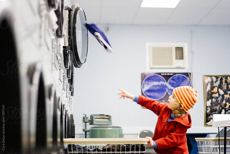 Boy throws clothes into a dryer at a laundromat by Cara Dolan for Stocksy United