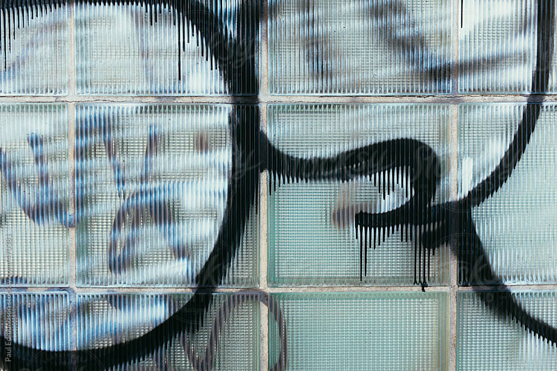 Spray painted graffiti on building windows, close up by Paul Edmondson for Stocksy United