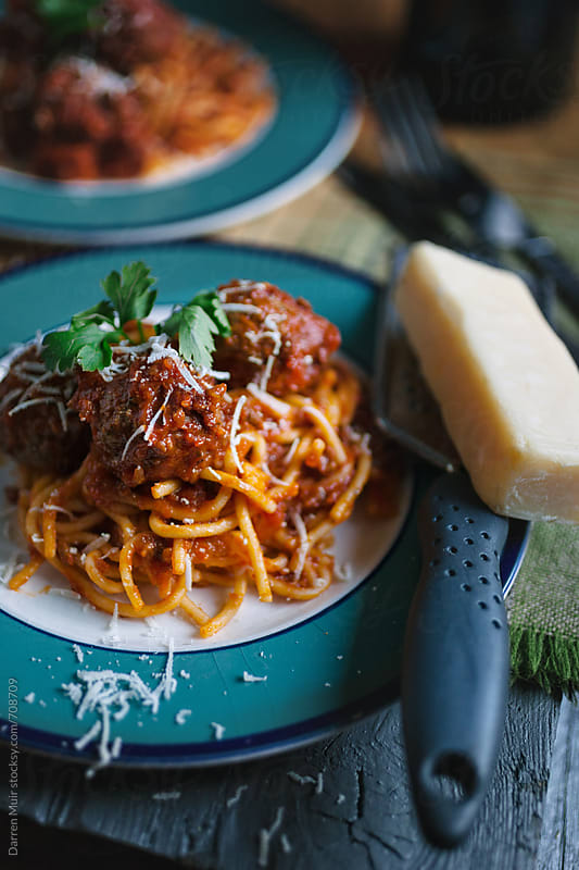 Two plates of spaghetti on a table with grated Parmesan. by Darren Muir for Stocksy United