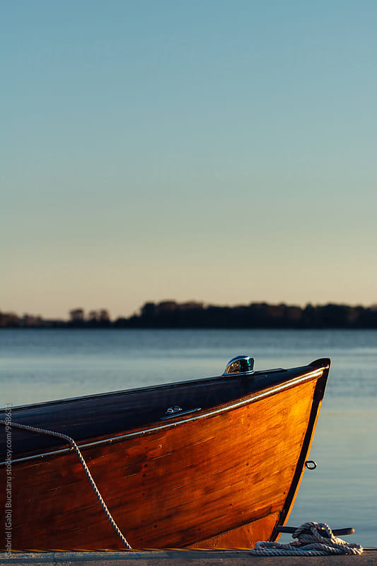 Wooden boat docked by a lake by Gabriel (Gabi) Bucataru for Stocksy United
