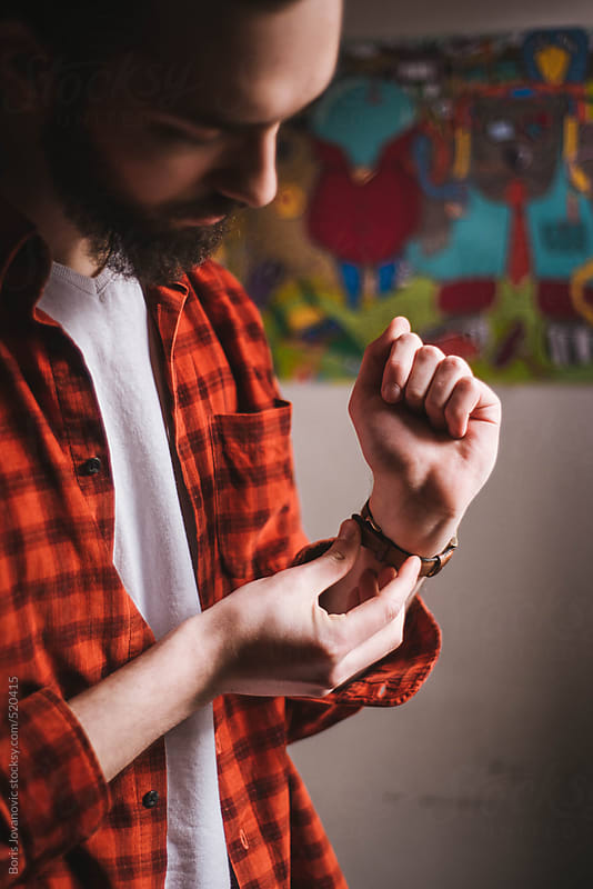 Bearded man setting up his watch by Boris Jovanovic for Stocksy United
