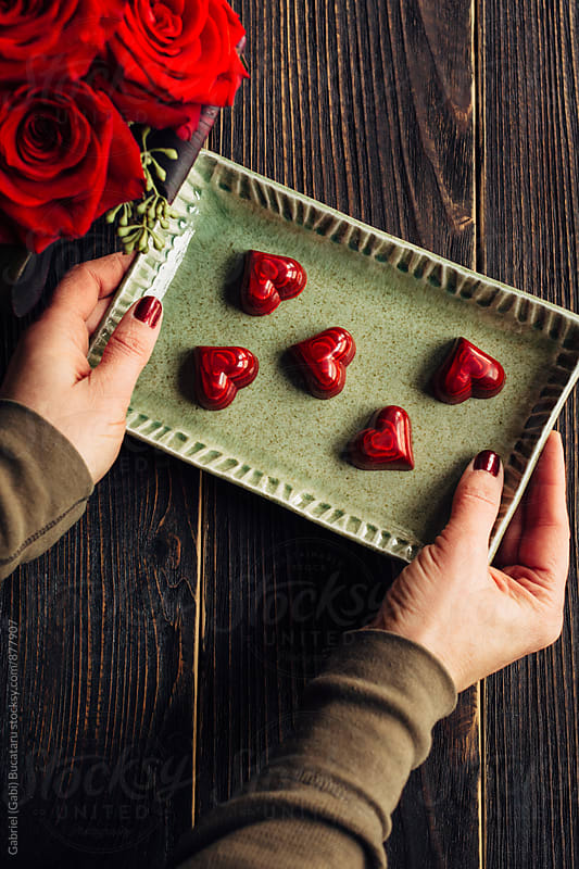 Woman's hands holding a tray with red heart shaped chocolates by Gabriel (Gabi) Bucataru for Stocksy United