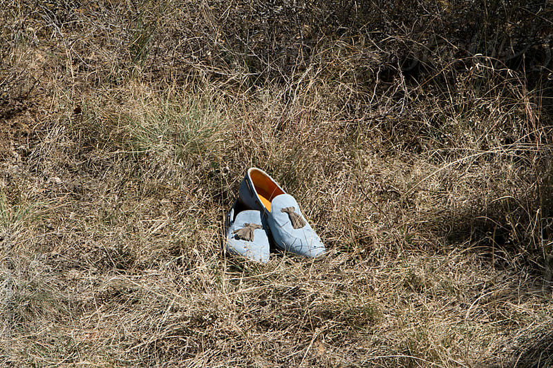 Blue shoes on dry grass by Victor Deschamps for Stocksy United