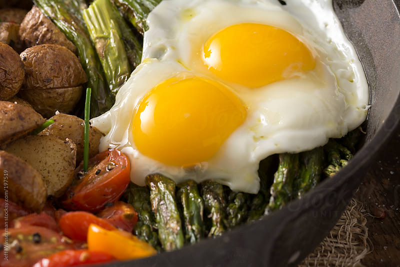 Breakfast:  Fried Eggs on Grilled Asparagus, Potatoes and Cherry Tomatoes by Studio Six for Stocksy United