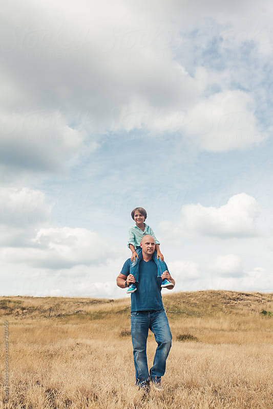 Man walking in a field carrying a little boy on his shoulders by Cindy Prins for Stocksy United