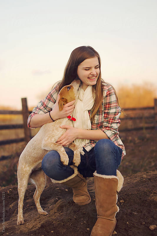 Puppy kissing young girl.  by Tana Teel for Stocksy United