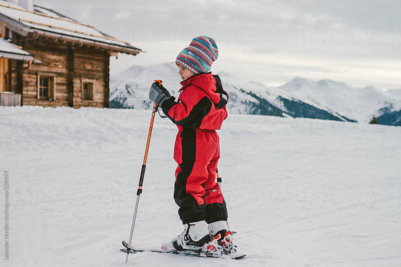 young boy on ski in front of an alpine cabin in winter landscape by Leander Nardin for Stocksy United
