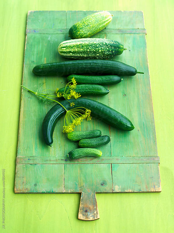 Variety of cucumbers on a green cutting board by J.R. PHOTOGRAPHY for Stocksy United