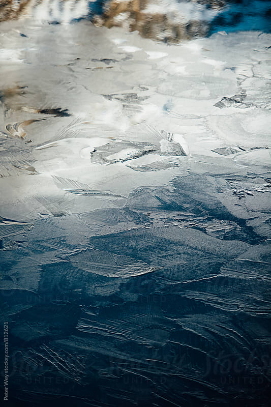 Frozen surface of an alpine lake by Peter Wey for Stocksy United