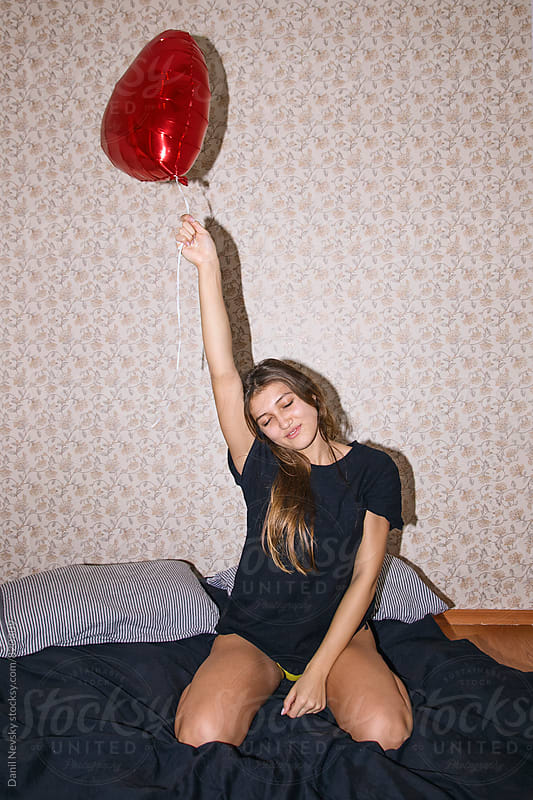 Young woman holding red shaped balloon by Danil Nevsky for Stocksy United