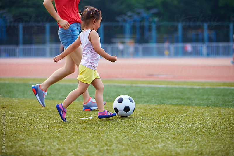 little girl playing football outdoor in the football field by Bo Bo for Stocksy United