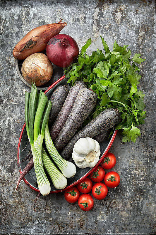 Assorted vegetables on a metal work surface by James Ross for Stocksy United