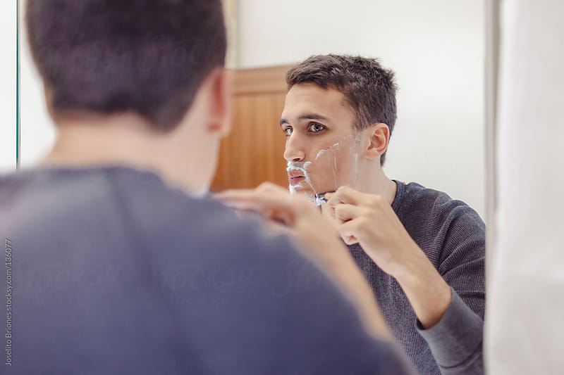 Young Mexican-American Starts the Day by Shaving by Joselito Briones for Stocksy United