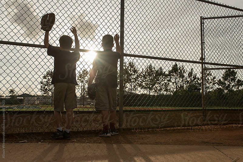 Two Boys Stand On A Ball Field At The Chain Link Fence by Alison Winterroth for Stocksy United