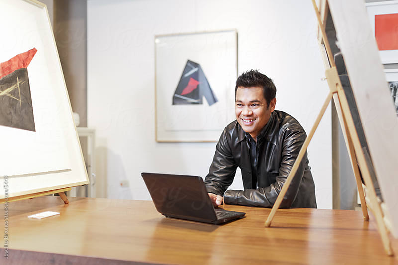 Art Gallery Owner Using Computer to Manage Business by Joselito Briones for Stocksy United