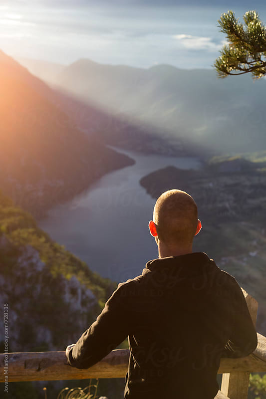 Young man enjoying the landscape at sunset by Jovana Milanko for Stocksy United