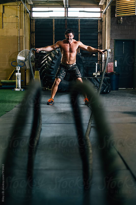 A muscular man exercises using battling ropes by Riley J.B. for Stocksy United