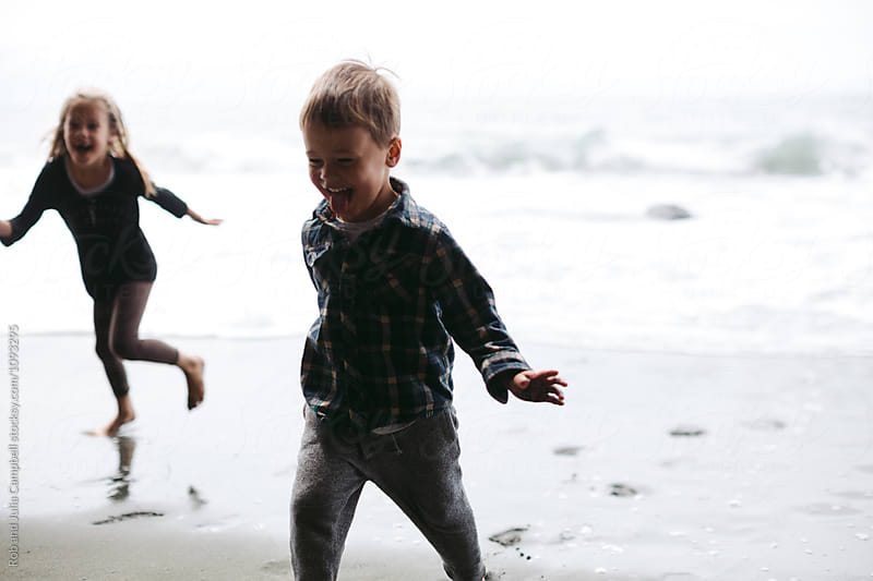 Young kids running away from ocean waves in winter or spring by Rob and Julia Campbell for Stocksy United