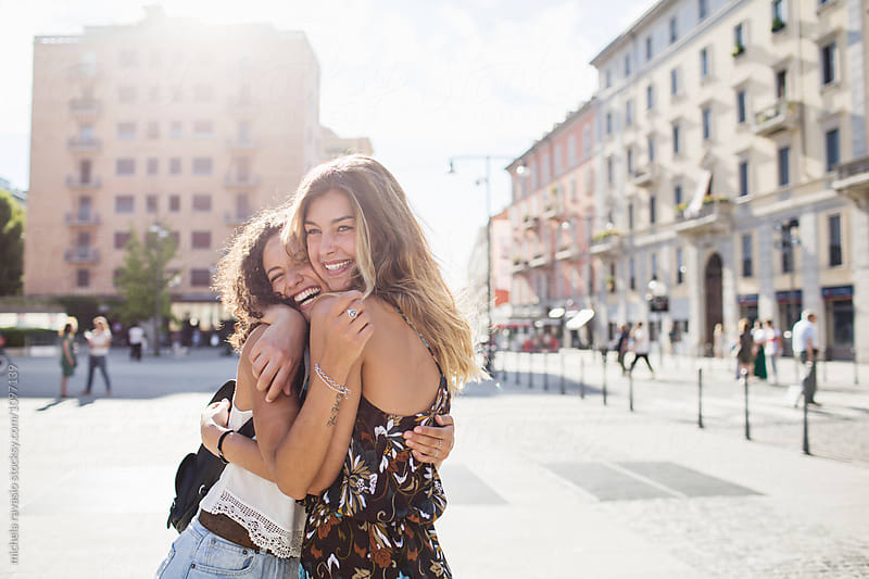 Two happy girls embrace each other by michela ravasio for Stocksy United