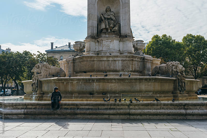 Boy sitting alone with birds on fountain in Europe by Trent Lanz for Stocksy United