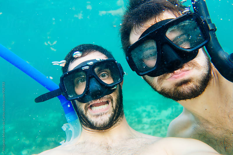 Two bearded man making faces underwater by Alejandro Moreno de Carlos for Stocksy United