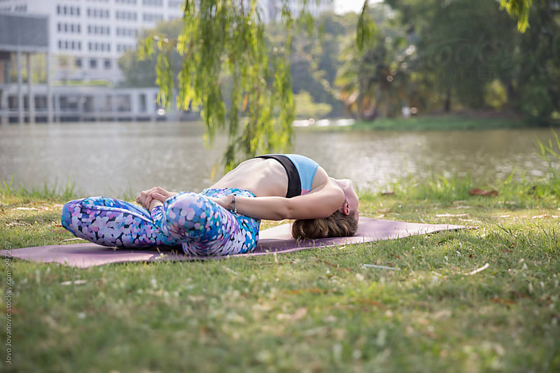 Yoga in a park - woman exercising outdoors by Jovo Jovanovic for Stocksy United