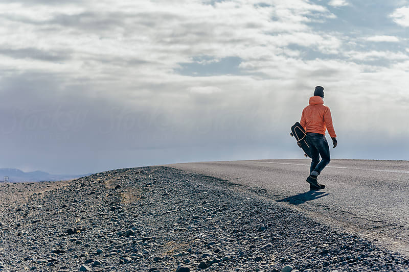 Man crossing the road with skateboard in Iceland by Soren Egeberg for Stocksy United