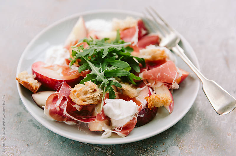 Burrata, peach and Iberico Ham salad. by Helen Rushbrook for Stocksy United