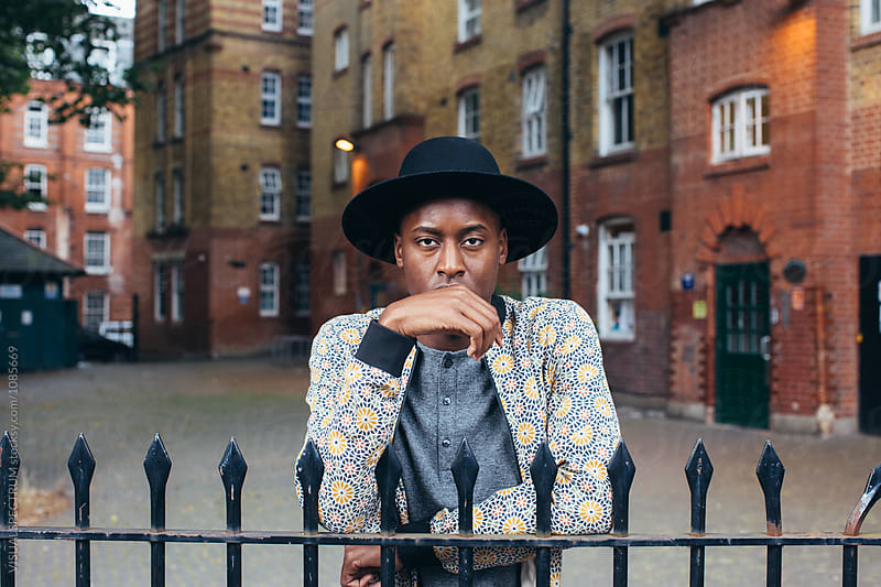London Street Style - Outdoor Portrait of Young Cool Black Man Standing Behind Fence in Working Class Neighborhood by Julien L. Balmer for Stocksy United