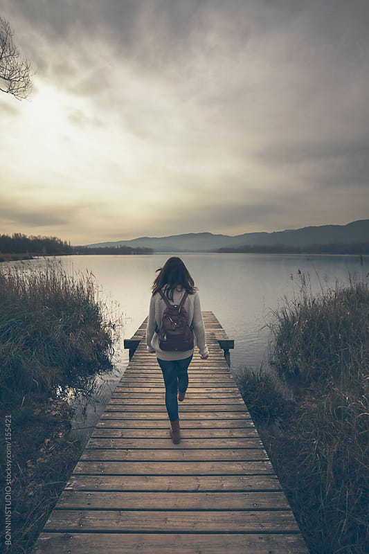 Young hipster woman walking on dock at lakeshore. by BONNINSTUDIO for Stocksy United